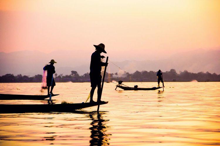 Silhouette Fishermen Against Sky During Sunset