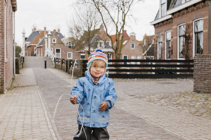 Portrait Of Baby Girl Holding String While Standing On Road In City
