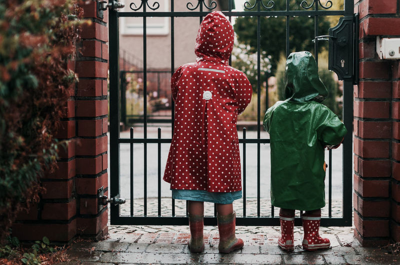 Rear view of children wearing raincoat while standing against gate
