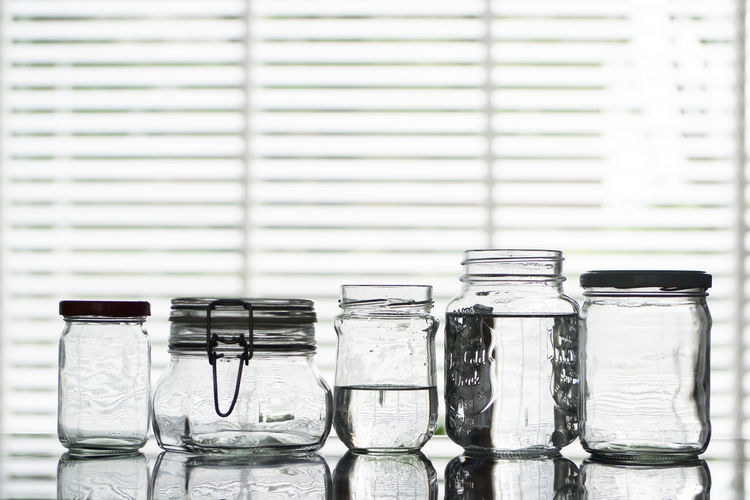 Reusable minimal waste canning jars. Sustainable products. Container Glass - Material Indoors  Transparent No People Jar Still Life Side By Side Focus On Foreground Group Of Objects Close-up Variation Bottle In A Row Table Food And Drink Choice White Background Day Order Mason Jar Masonjar Reusable Recycled Materials Glass Jars Glass Jars On The Table Canning Jars Minimal Waste Waste Reused Materials Reused Sustainable Ecofriendly Water