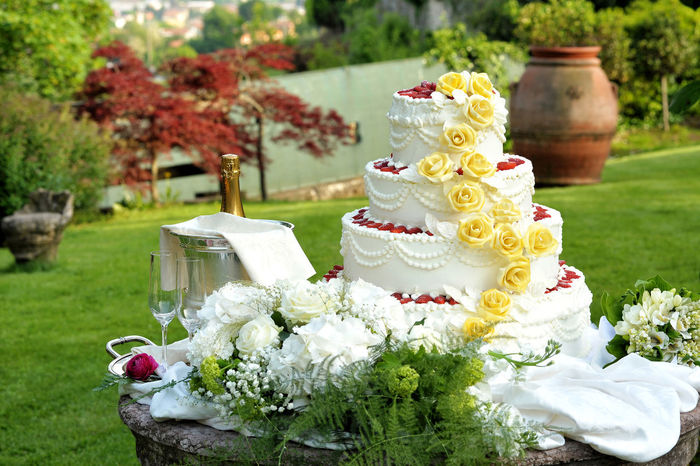 Large tiered decorative wedding cake with trailing yellow icing roses displayed on a table outdoors in a park or garden with fresh white flowers and a bottle of champagne to toast the celebration Icing Love Romance Romantic Tiered Baking Bridal Cake Decorative Dessert Flower Food And Drink Life Events Marriage  Ready-to-eat Sweet Food Temptation Wedding Wedding Cake