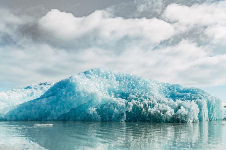 Iceberg floating in sea against sky