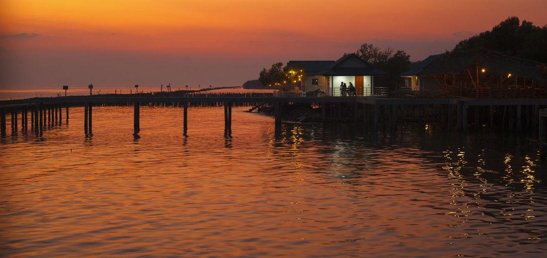 Wooden posts in sea against orange sky