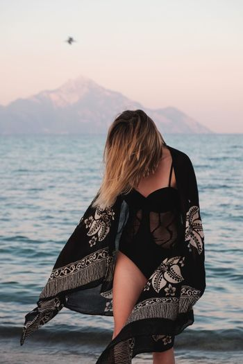 Woman in black swimsuit wearing shawl on shore during sunset