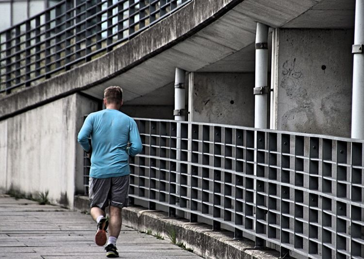 Rear view of man jogging in city