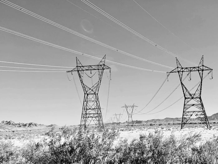 Black and white low angle view of electricity pylon on field against sky