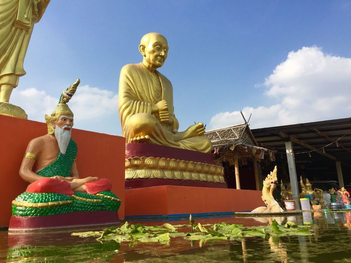 Golden buddha Sculpture Representation Statue Human Representation Art And Craft Male Likeness Architecture Spirituality Gold Colored Creativity Cloud - Sky Belief Place Of Worship Sky Religion Built Structure No People Building Nature Idol