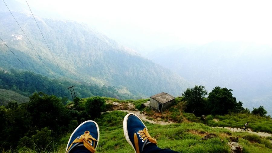 Low Section Of Person Legs Against Mountains During Foggy Weather