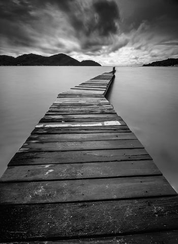 Old wooden jetty with stormy clouds in the horizon. Beach Beauty In Nature Blackandwhite Cloud - Sky Clouds And Sky Jetty Lake Landscape Long Exposure Monochrome Mountain Nature Old Outdoors Scenics Sky Storm Cloud Textured  The Way Forward Tranquility Travel Destinations Water Water's Edge Wodden Footbridge Wood - Material