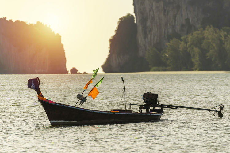 long tail fishing boat at the sunrise Calm Holidays Morning Nature Old Boat Sunny Sky Travel Beach Bouy Colorful Colors Flag Dawn Fishing Boat Island Life At Sea Long Tail Boat Nobody Ocean Propeller Rock Islands Sand And Sea Sea Sunrise Sunset Vacation
