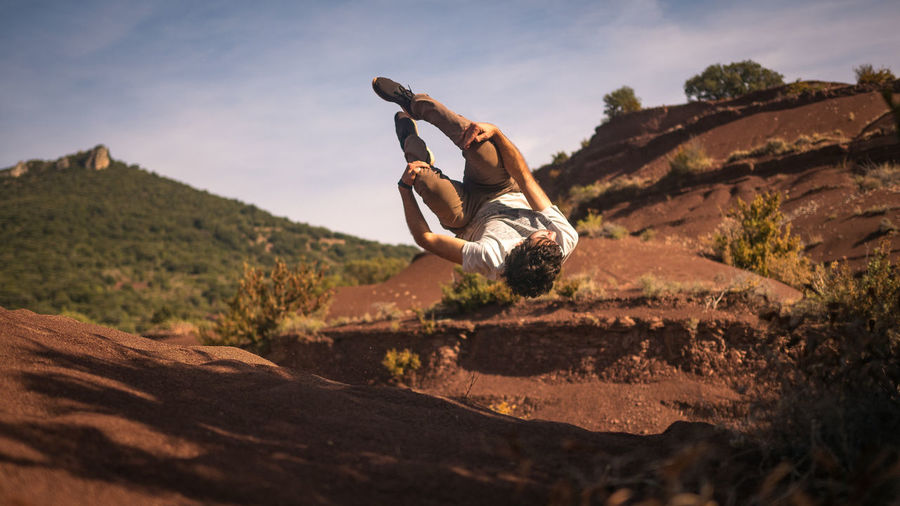 Low Angle View Of Man Practicing Stunt Against Rock Formations