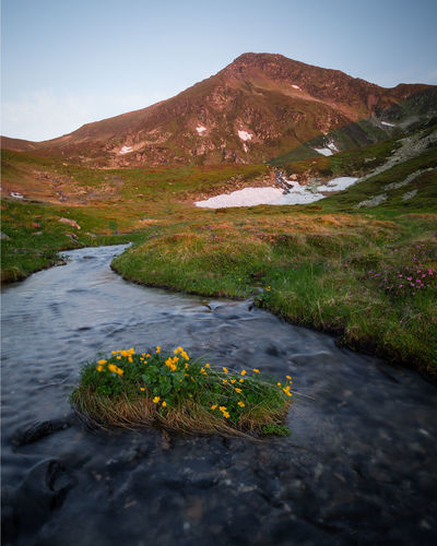 Scenic view of river stream amidst mountains against sky