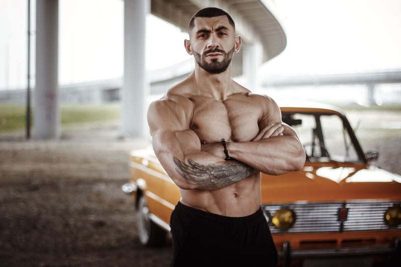 Portrait of shirtless muscular man standing by car on field