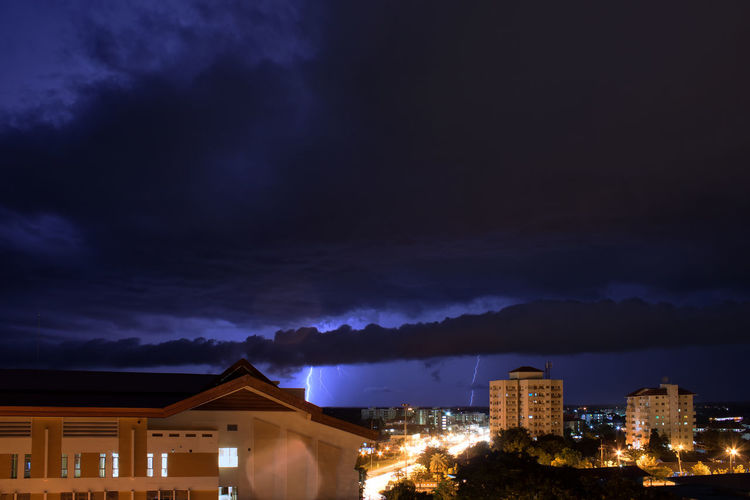 Illuminated buildings against cloudy sky at night