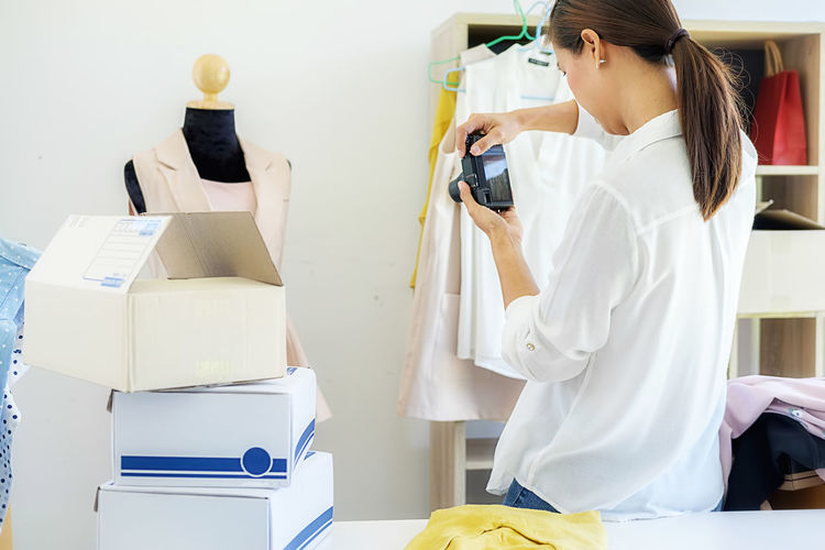 Fashion Designer Photographing Dress In Office