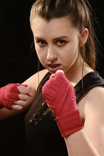 Close-up portrait of female boxer against black background