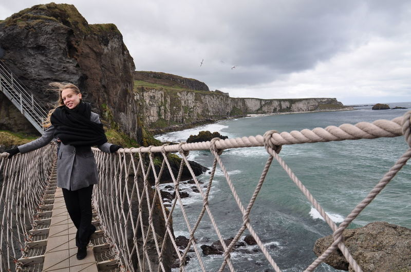 Full length portrait of woman standing on footbridge at coastline