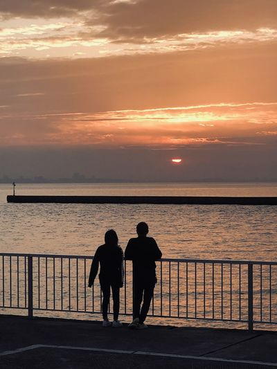Silhouette men standing on railing against sea during sunset