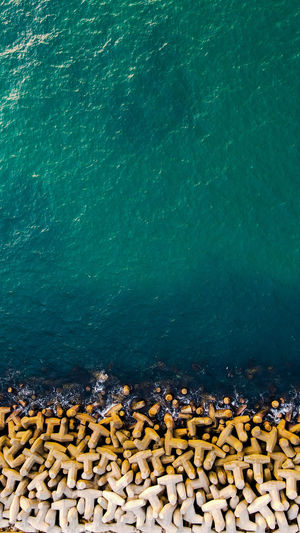 Aerial drone view over the sea and the breakwater at a sunny summer day