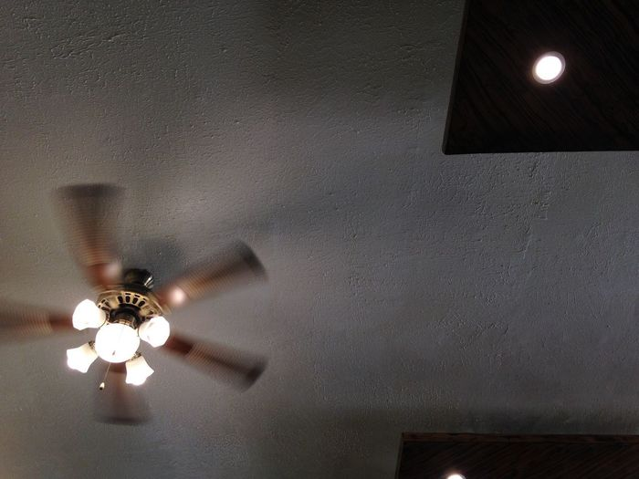 Fan in motion Ceiling Ceiling Fan Electricity  Lighting Equipment Home Interior Fan Indoors  Low Angle View Electric Fan Illuminated Architecture No People Built Structure Blurred Motion Motion Light Electric Lamp Hanging