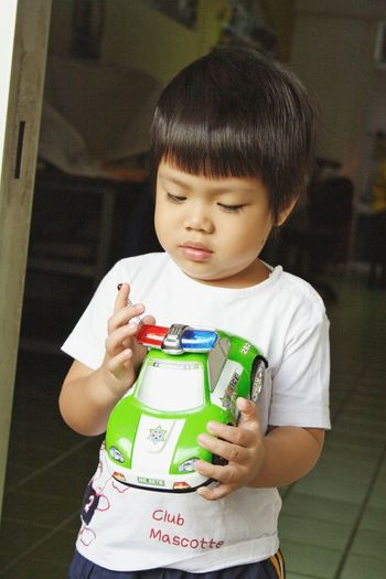 Close-up of cute baby boy holding toy car