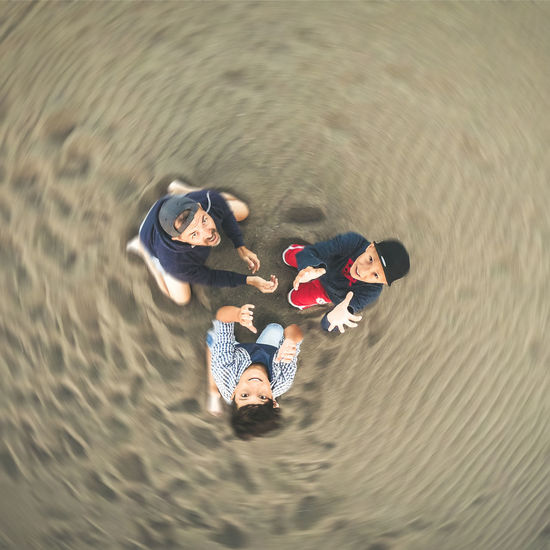High angle portrait of father and sons sitting on sand at beach