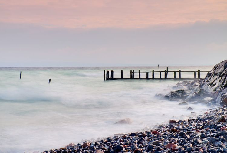 Abandoned wooden wharf in sea within blue pink color of sky, blur waves on water level.