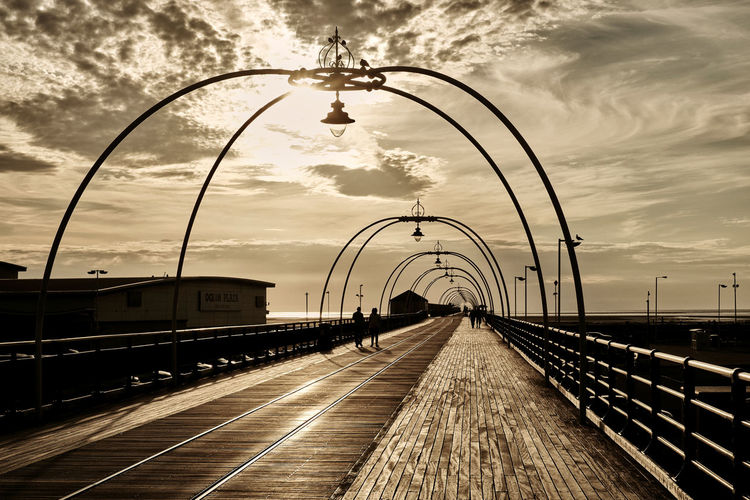 LONG WALK ON A LONG PIER: Evening strollers on Southport Pier, the second longest in Britain. (Southend's is longer.) The pier was built in 1860 and has been altered several times since. The rails on the left are for an intermittently-operated tram service. Southport, Merseyside. Sepia Distance Wooden Floor People Walking  Tramway Architecture Built Structure Cloud - Sky Diminishing Perspective Direction Lighting Equipment Mode Of Transportation Motion Nature Outdoors Public Transportation Sky Street Street Light Sunset The Way Forward Track Transportation