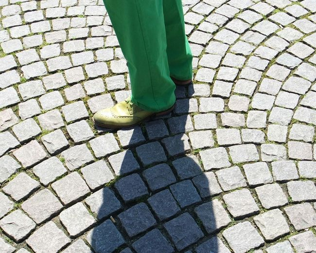 Low section of man standing on cobbled street
