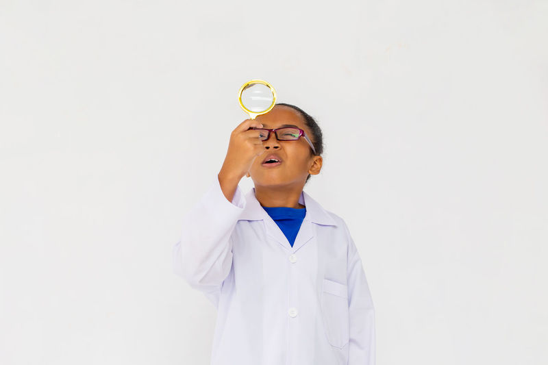 Girl looking away while standing against white background