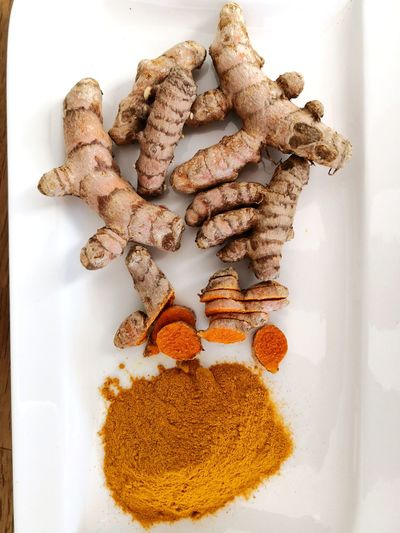 Turmeric powder and curcuma roots on white plate background Curcumin Health Benefits Digestion Turmeric  Curcuma Curcuma Root Turmeric Powder Turmeric Root EyeEm Selects Close-up Food And Drink Various Ground - Culinary For Sale
