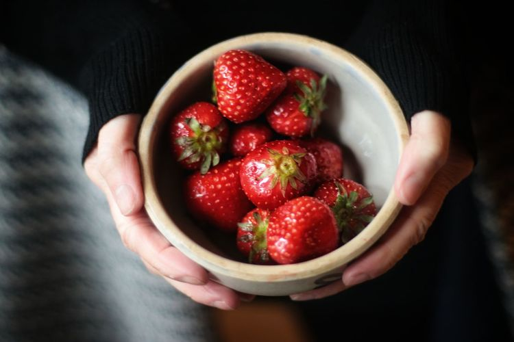 Hand holding strawberries in bowl