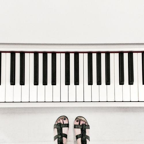 Low section view of woman standing by piano