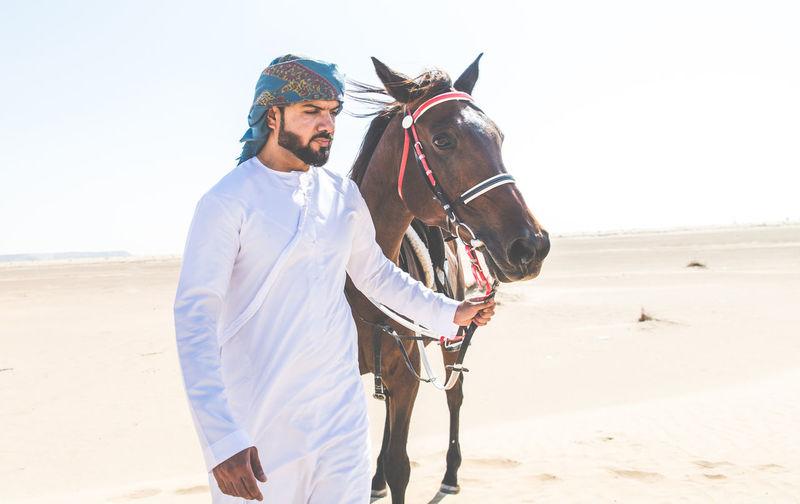 Man with horse walking in desert
