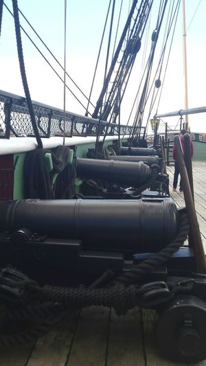 Frigate Naval Ship Warship Deck Wooden Deck Canon Gun Gunports Historic Sailing Ship Tall Ship Nautical Vessel Mode Of Transport Transportation Wooden Ship Ropes And Lines Sky Cloud - Sky Ships Rigging Built Structure Ships Bow Bowsprit Ropes Shrouds Bulwark
