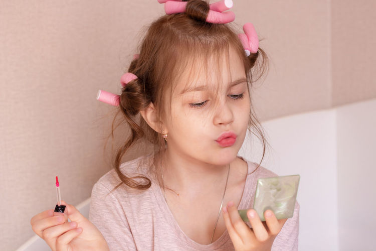 Portrait of happy girl holding pink indoors