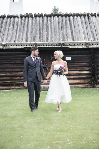 Smiling Bride And Groom Holding Hands In Yard