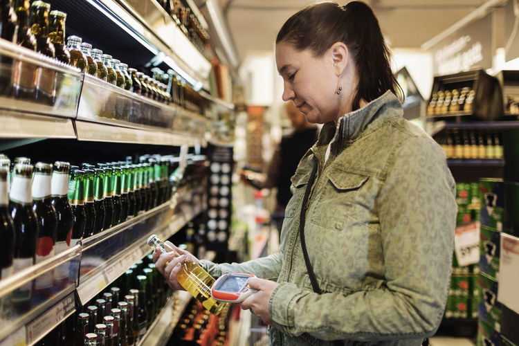 Full length of woman standing by bottles at store