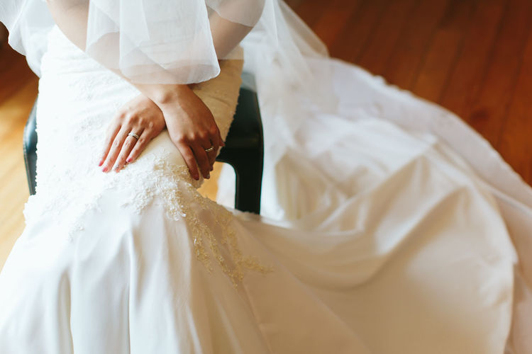 Midsection of bride sitting on stool in wedding ceremony