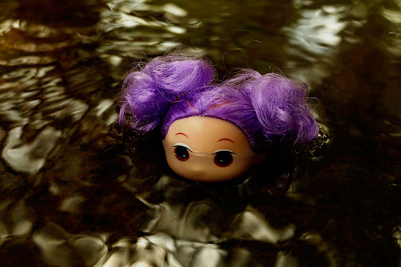 Close-Up Of Abandoned Doll In Puddle