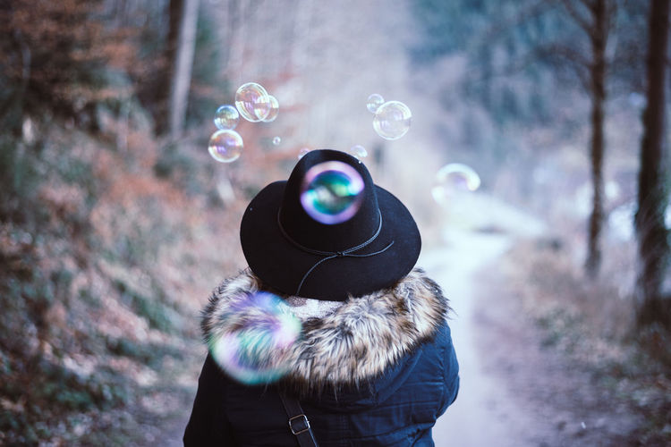 Bubblehat Adult Adults Only Autumn Back Bubbles Close-up Day Elegant Focus On Foreground Forest Hat Human Body Part Leisure Activity Multi Colored One Person One Woman Only Outdoors People Real People Smoking Soap Bubbles Springtime Unusual Warm Clothing Woman Rethink Things AI Now