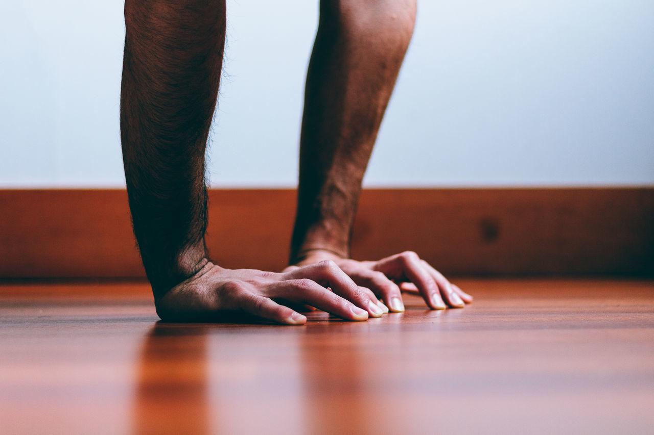Cropped image of hand on hardwood floor