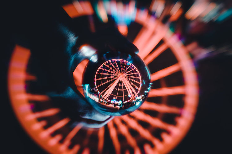 Close-up of illuminated ferris wheel against black background