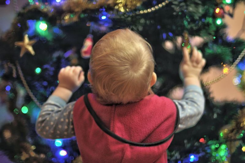 Rear view of baby girl standing by christmas tree at home