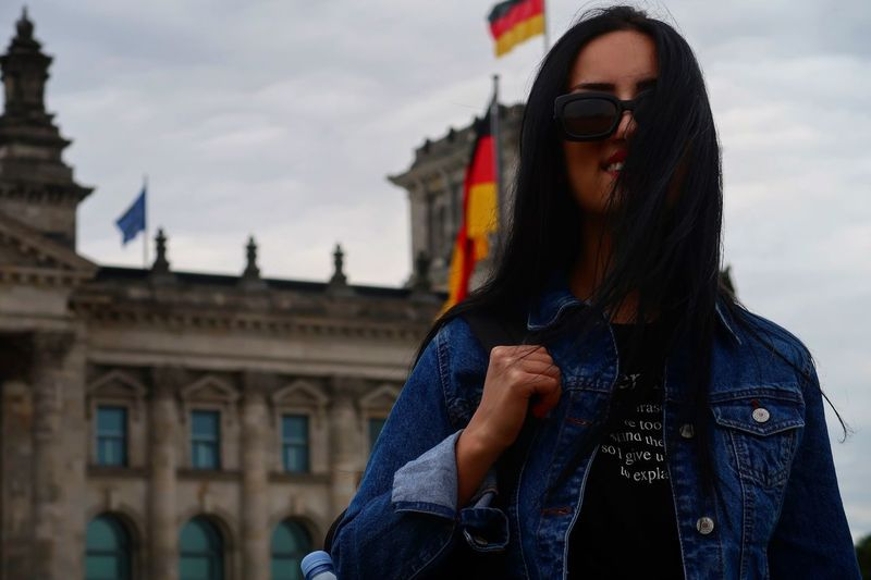 Young woman standing outside reichstag building in city