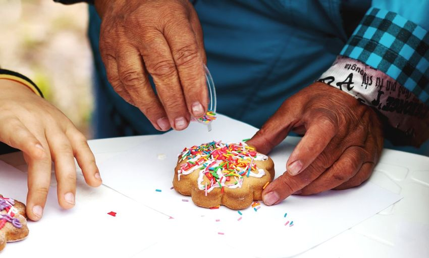Only hands. aged woman decorates cookies.