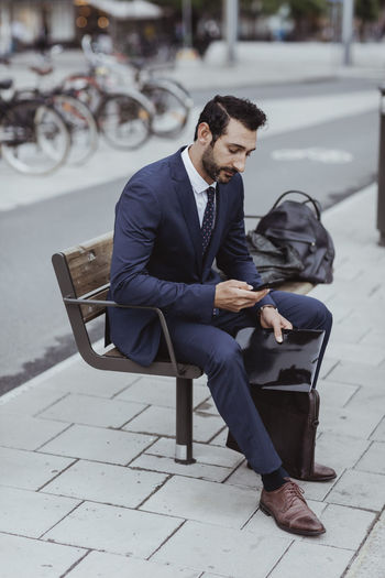 Young man using mobile phone while sitting on seat