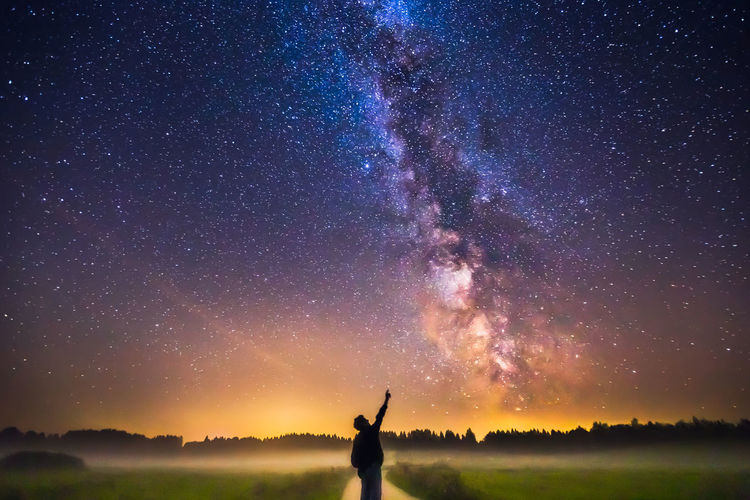Man standing against star field at night
