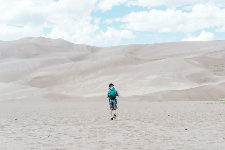 Rear view of boy on sand against sky