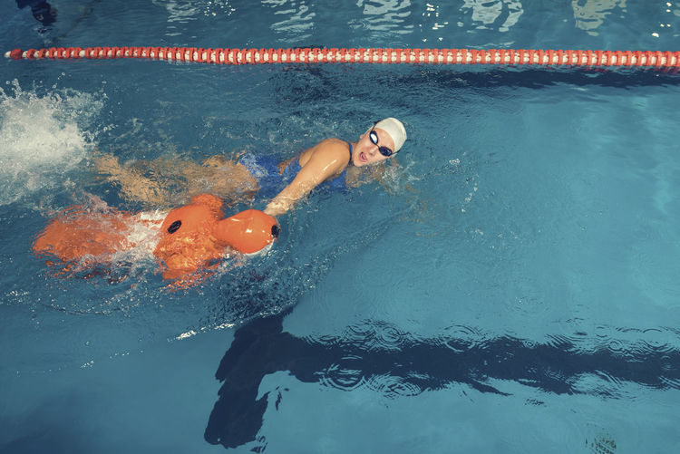 Woman with cpr dummy standing at swimming pool